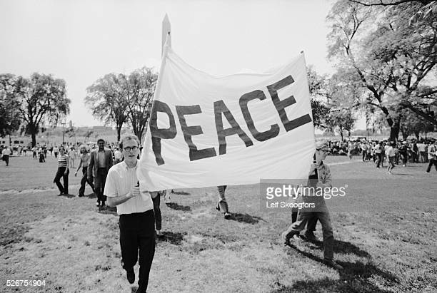 """Anti-Vietnam War protesters in Washington DC hold a sign that reads """"Peace"""" during a demonstration for the students killed at Kent State."""