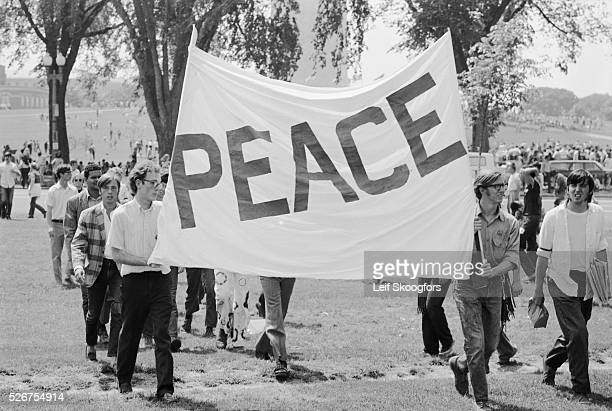 "Anti-Vietnam War protesters in Washington DC hold a sign that reads ""Peace"" during a demonstration for the students killed at Kent State."
