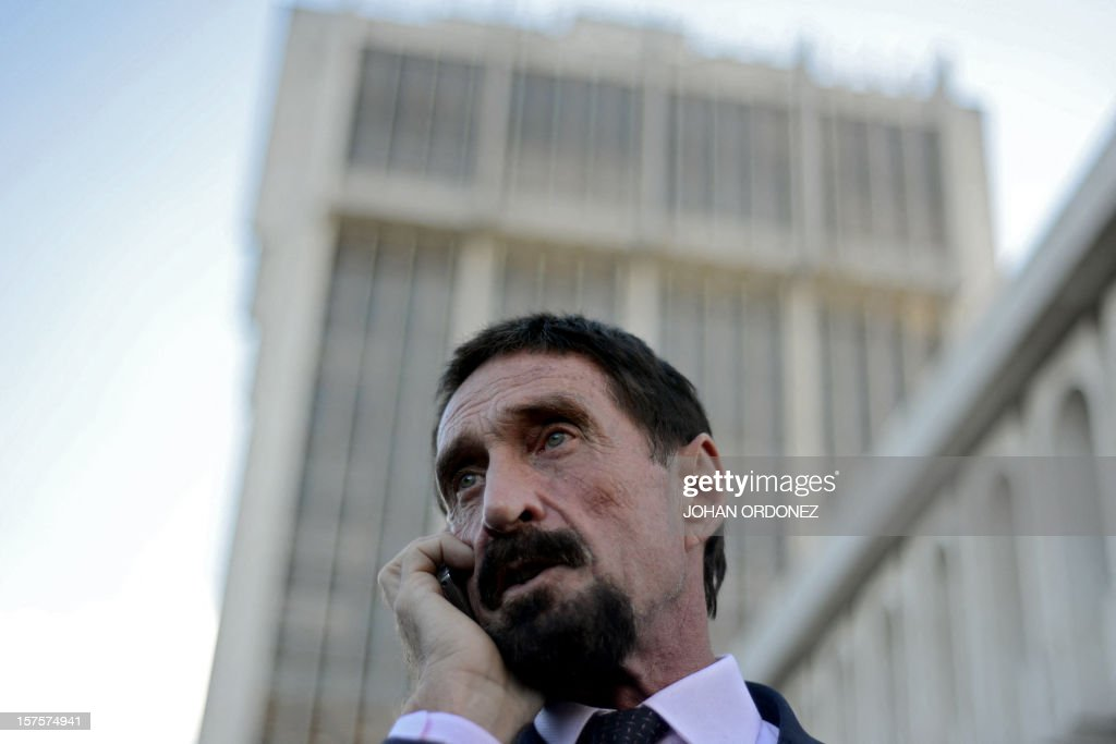 US anti-virus software pioneer John McAfee speaks on his mobile phone in front of the Supreme Court in Guatemala City on December 04, 2012. McAfee, wanted for questioning over the murder of his neighbor last month in Belize, is seeking political asylum in Guatemala. AFP PHOTO / Johan ORDONEZ