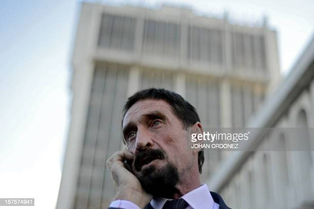 Anti-virus software pioneer John McAfee speaks on his mobile phone in front of the Supreme Court in Guatemala City on December 04, 2012. McAfee,...