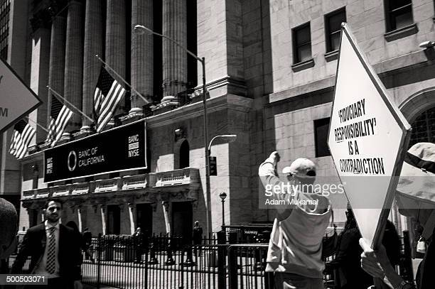 """Anti-Wall Street activist holding a sign that reads """"Fiduciary Responsibility is a Contradiction"""" Wall Street in front of the New York Stock Exchange."""