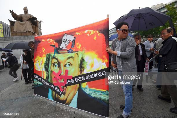 Antiwar activists hold a banner showing a caricature of US President Donald Trump during an antiTrump rally near the US embassy in Seoul on September...