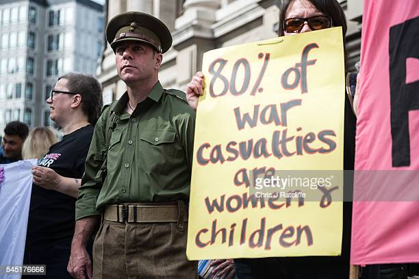 Anti-war poet, John Poet, dresses as a soldier alongside other demonstrators outside the Queen Elizabeth II conference centre on July 6, 2016 in...