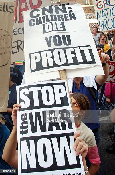Antiwar protesters hold signs that criticize Cable News Network's coverage of the USled war against Iraq during a demonstration March 22 2003 in...