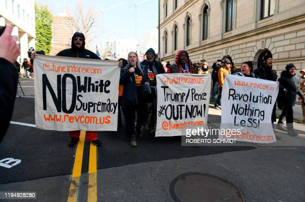 Antiwhite supremacy protesters hold banners as they shout antiTrump slogans at the end of a rally by gun supporters outside the Virginia State...
