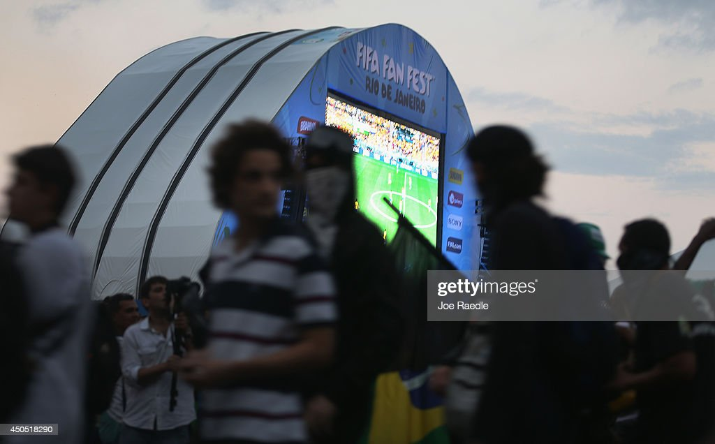 Anti-World Cup protesters walk past the giant screen at the FIFA fan fest on Copacabana beach on June 12, 2014 in Rio de Janeiro, Brazil. Brazil defeated Croatia 3-1 in the first match of 2014 FIFA World Cup today.