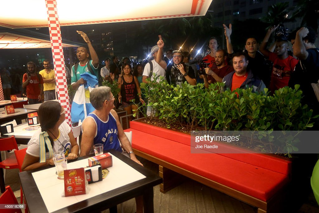 Anti-World Cup protestors yell at people watching the game at a restaurant on Copacabana beach on June 12, 2014 in Rio de Janeiro, Brazil. Brazil defeated Croatia 3-1 in the first match of 2014 FIFA World Cup today.