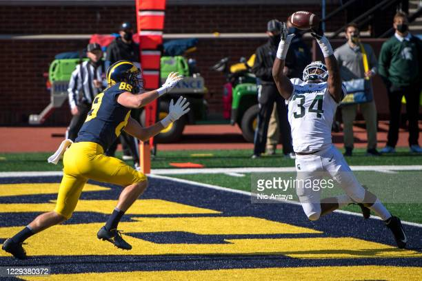 Antjuan Simmons of the Michigan State Spartans disrupts a pass intended for Carter Selzer of the Michigan Wolverines during the second quarter at...
