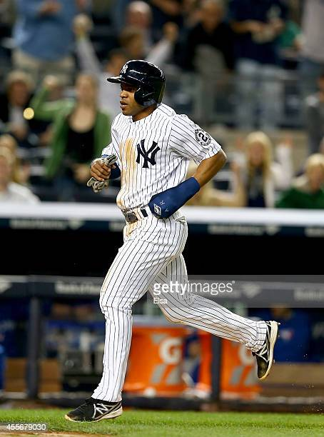Antoan Richardson of the New York Yankees scores the game winning run on a hit by teammate Chase Headley in the bottom of the ninth inning against...