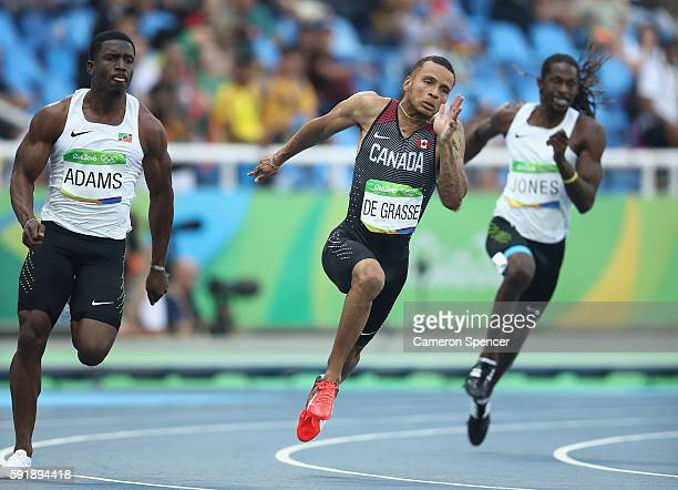 Antoine Adams of Saint Kitts and Nevis Andre de Grasse of Canada and Brandon Jones of Belize compete during the Men's 200m Round 1 on Day 11 of the...