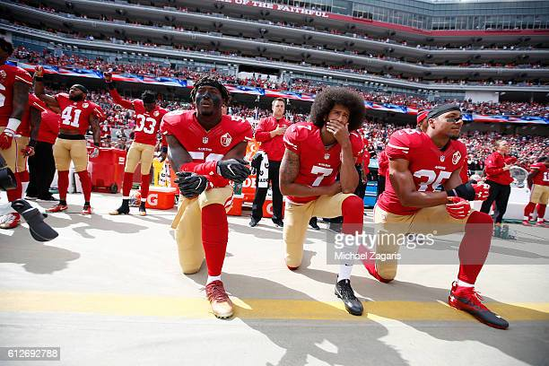 Antoine Bethea and Rashard Robinson of the San Francisco 49ers raise their first during the anthem as Eli Harold while teammates Colin Kaepernick and...