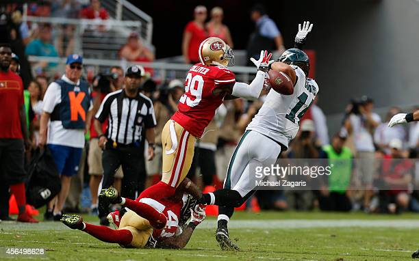 Antoine Bethea of the San Francisco 49ers knocks over Riley Cooper of the Philadelphia Eagles as Chris Culliver strips the ball away form him during...