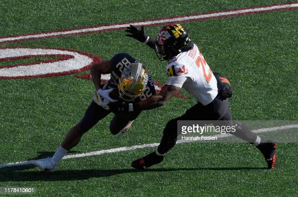 Antoine Brooks Jr #25 of the Maryland Terrapins tackles Demetrius Douglas of the Minnesota Gophers during the first quarter of the game at TCF Bank...