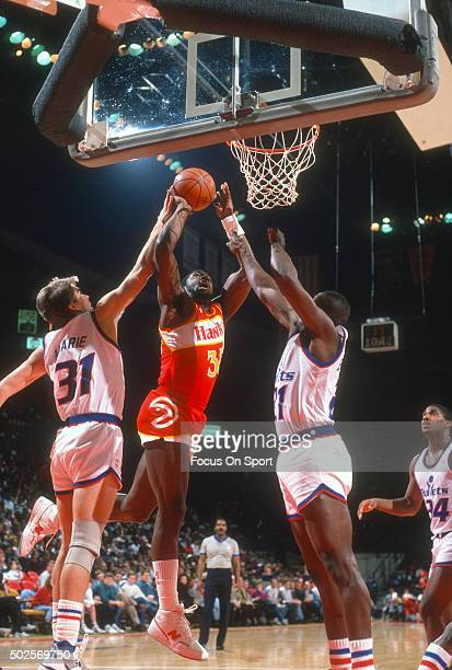 Antoine Carr of the Atlanta Hawks shoots over Ledell Eackles and Mark Alarie of the Washington Bullets during an NBA basketball game circa 1988 at...
