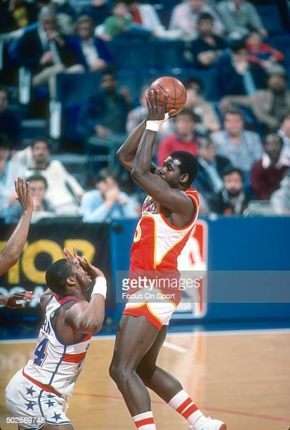 Antoine Carr of the Atlanta Hawks shoots over Rick Mahorn of the Washington Bullets during an NBA basketball game circa 1985 at the Capital Centre in...