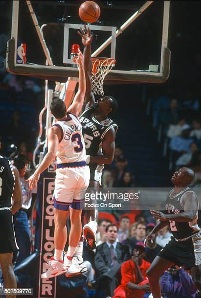 Antoine Carr of the San Antonio Spurs attempts to block the shot of Rex Chapman of the Washington Bullets during an NBA basketball game circa 1992 at...