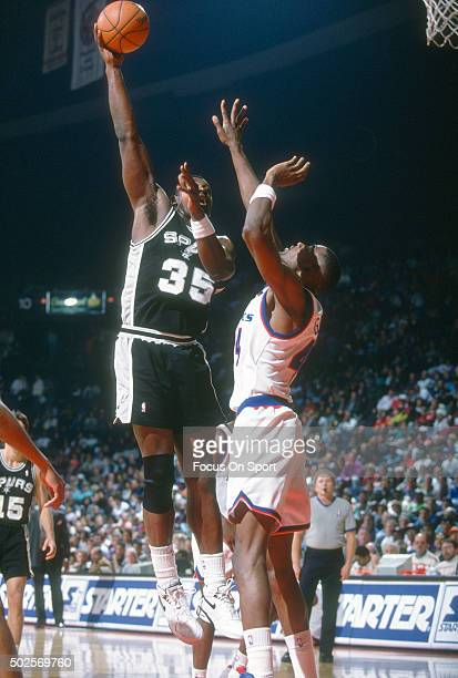 Antoine Carr of the San Antonio Spurs shoots over Harvey Grant of the Washington Bullets during an NBA basketball game circa 1992 at the Capital...