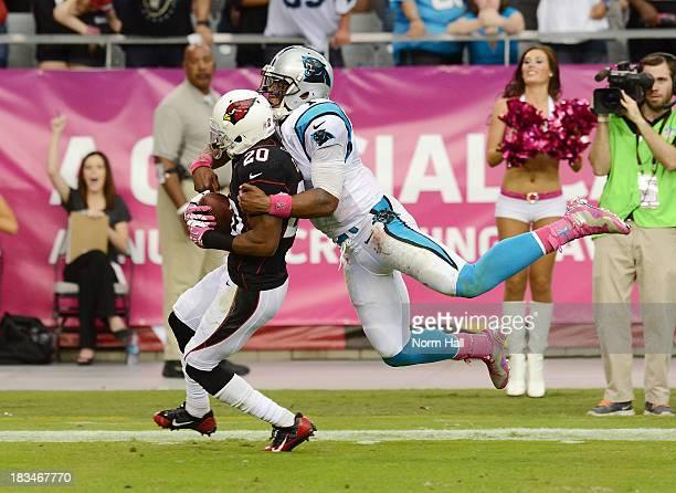 Antoine Cason of the Arizona Cardinals runs back an interception as Cam Newton of the Carolina Panthers makes a tackle at University of Phoenix...