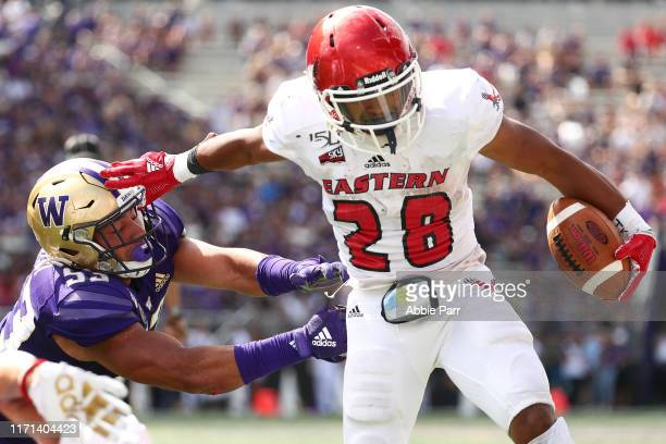 Antoine Custer Jr. #28 of the Eastern Washington Eagles breaks a tackle against MJ Tafisi of the Washington Huskies in the third quarter during their...