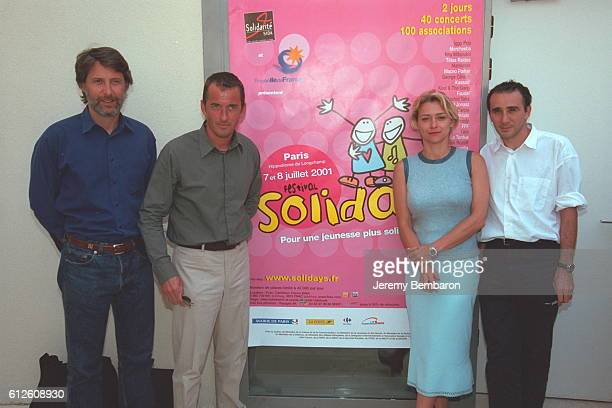Antoine de Caunes Christophe Dechavanne Valerie Payet and Elie Semoun in front of the 'Solidays' poster