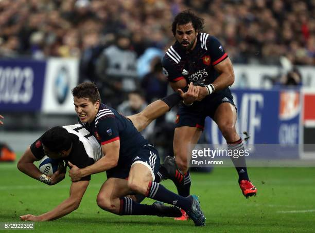 Antoine Dupont of France tackles Reiko Ioane of New Zealand during the Autumn International between France and New Zealand at the Stade de France on...