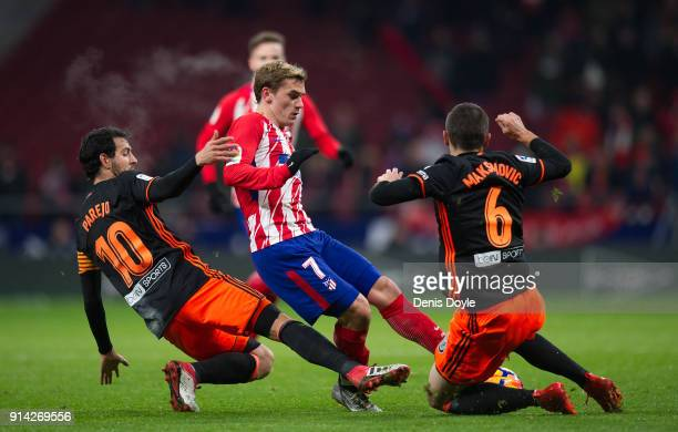 Antoine Greizmann of Atletico de Madrid is tackled by Daniel Parejo and Nemanja Maksimovic of of Valencia CF during the La Liga match between...