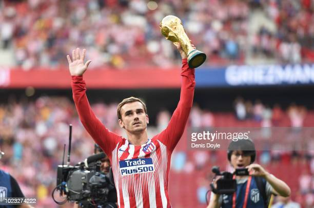 Antoine Greizmann of Club Atletico de Madrid holds up the FIFA World Cup trophy before the La Liga match between Club Atletico de Madrid and Rayo...
