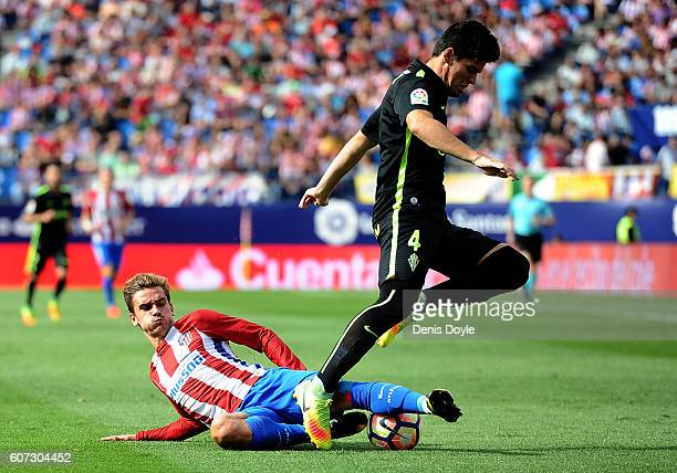 Antoine Greizmann of Club Atletico de Madrid steals the ball from Jorge Mere of Sporting Gijon during the La Liga match between Club Atletico de...