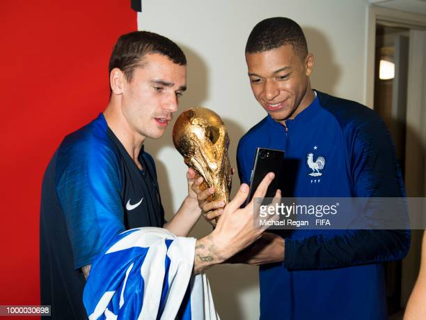 Antoine Griezmann and Kylian Mbappe of France pose with the Champions World Cup trophy after the 2018 FIFA World Cup Russia Final between France and...