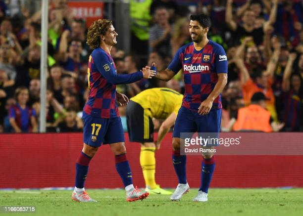 Antoine Griezmann and Luis Suarez of Barcelona celebrate as Ainsley MaitlandNiles of Arsenal scores an own goal for their first goal during the Joan...