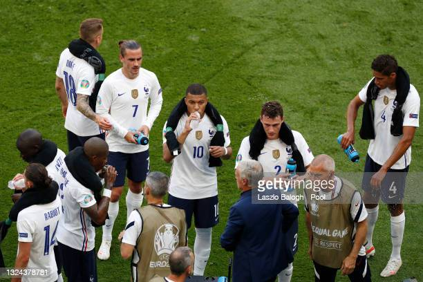 Antoine Griezmann, Kylian Mbappe and Benjamin Pavard of France drink during the drinks break in the UEFA Euro 2020 Championship Group F match between...