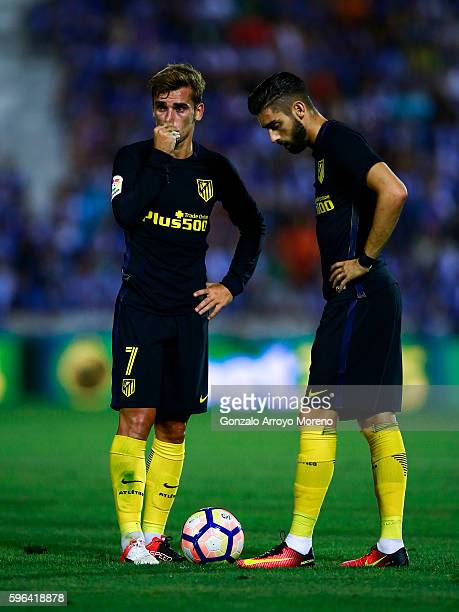 Antoine Griezmann of Atletico de Madrid and his teammate Yannick Carrasco react before striking the ball after a fault during the La Liga match...