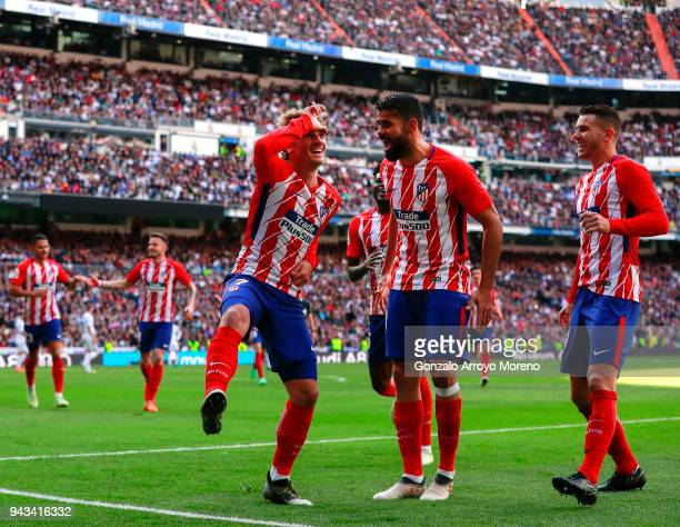 Antoine Griezmann of Atletico de Madrid celebrates scoring their opening goal with teammate Diego Costa during the La Liga match between Real Madrid...