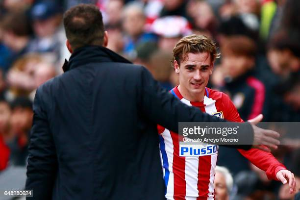 Antoine Griezmann of Atletico de Madrid clashes hands with his coach Diego Pablo Simeone as he leaves the pitch during the La Liga match between Club...