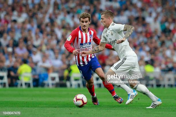 Antoine Griezmann of Atletico de Madrid competes for the ball with Toni Kroos of Real Madrid CF during the La Liga match between Real Madrid CF and...