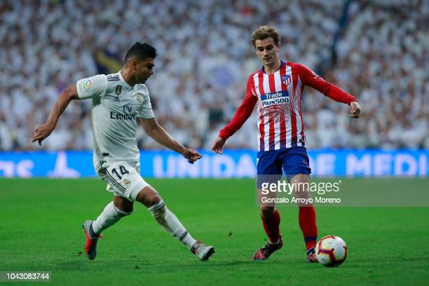 Antoine Griezmann of Atletico de Madrid competes for the ball with Carlos Casemiro of Real Madrid CF during the La Liga match between Real Madrid CF...