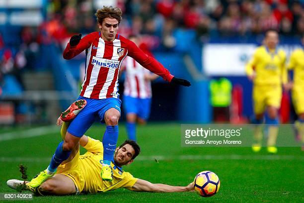 Antoine Griezmann of Atletico de Madrid competes for the ball with Pedro Bigas of UD Las Palmas during the La Liga match between Club Atletico de...