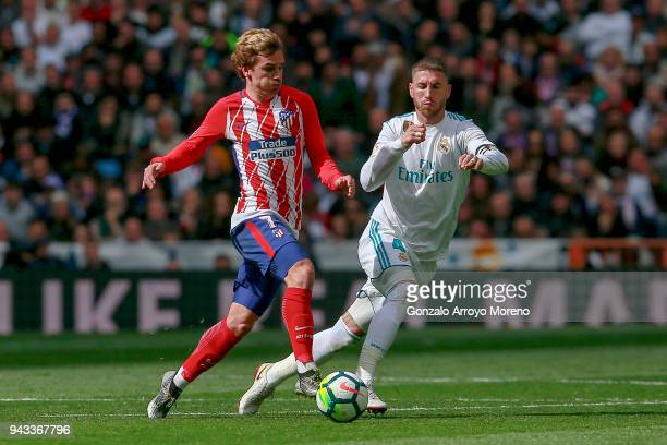 Antoine Griezmann of Atletico de Madrid competes for the ball with Sergio Ramos of Real Madrid CF during the La Liga match between Real Madrid CF and...
