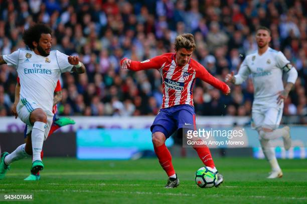 Antoine Griezmann of Atletico de Madrid competes for the ball with Marcelo of Real Madrid CF and his teammate Sergio Ramos during the La Liga match...