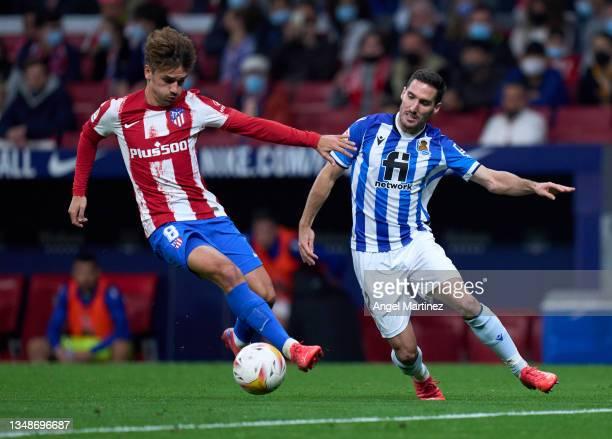 Antoine Griezmann of Atletico de Madrid competes with Joseba Zaldua of Real Sociedad during the LaLiga Santander match between Club Atletico de...
