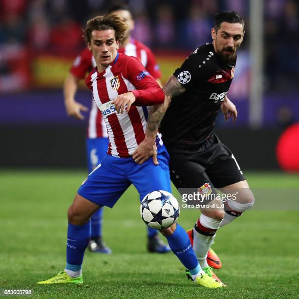 Antoine Griezmann of Atletico de Madrid competes with Roberto Hilbert of Bayer Leverkusen during the UEFA Champions League Round of 16 second leg...