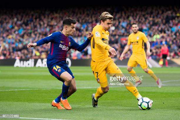 Antoine Griezmann of Atletico de Madrid controls the ball under pressure from Philippe Coutinho of FC Barcelona during the La Liga match between...