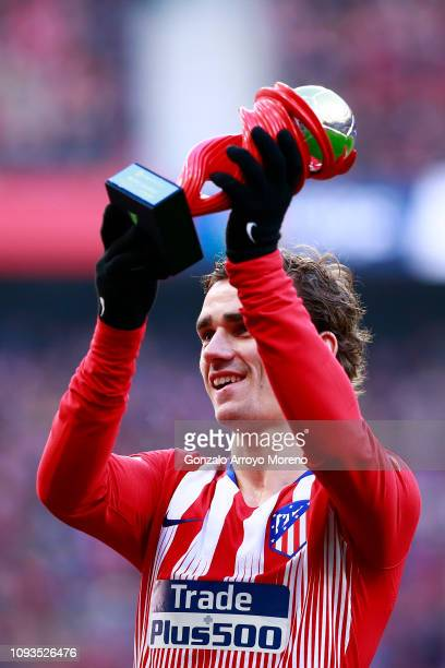 Antoine Griezmann of Atletico Madrid celebrates with a trophy after being awarded La Liga Player of the Month for December prior to the La Liga match...