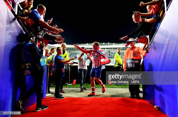 Antoine Griezmann of Atletico Madrid celebrates with fans as he walks off the pitch following the UEFA Super Cup between Real Madrid and Atletico...