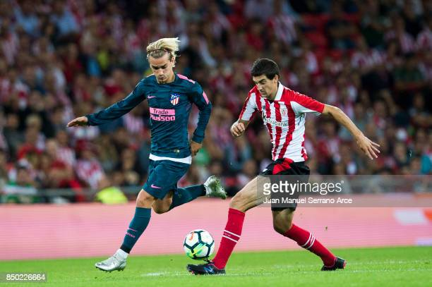 Antoine Griezmann of Atletico Madrid competes for the ball with Mikel San Jose of Athletic Club during the La Liga match between Athletic Club and...