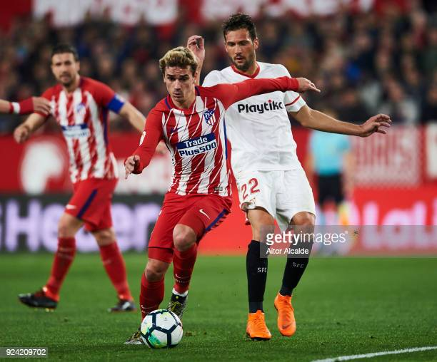 Antoine Griezmann of Atletico Madrid competes for the ball with Franco Vazquez of Sevilla CF during the La Liga match between Sevilla CF and Atletico...