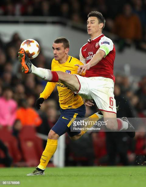 Antoine Griezmann of Atletico Madrid goes past Laurent Koscielny of Arsenal on his way to scoring his sides first goal during the UEFA Europa League...