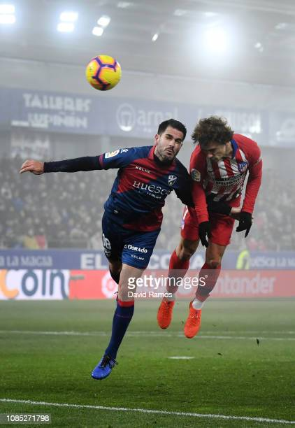 Antoine Griezmann of Atletico Madrid heads the ball under pressure from Pablo Insua of SD Huesca during the La Liga match between SD Huesca and Club...