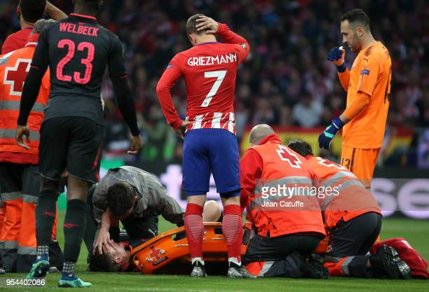 Antoine Griezmann of Atletico Madrid looks at his teammate in the French national team Laurent Koscielny of Arsenal seriously injured during the UEFA...