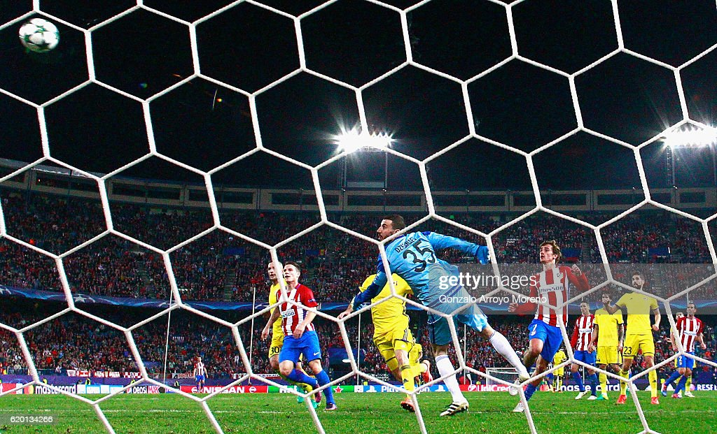 Antoine Griezmann of Atletico Madrid (R) scores his sides second goal by chipping the ball over Soslan Dzhanayev of FC Rostov (C) during the UEFA Champions League Group D match between Club Atletico de Madrid and FC Rostov at Vincente Calderon on November 1, 2016 in Madrid, Spain.